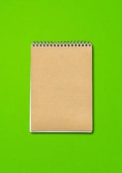 Spiral geschlossenes notizbuchmodell, braune papierabdeckung, lokalisiert auf grünem hintergrund