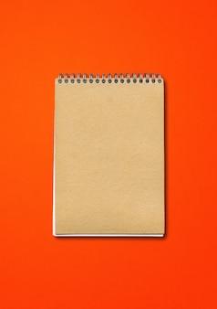 Spiral geschlossenes notizbuchmodell, braune papierabdeckung, lokalisiert auf rotem hintergrund