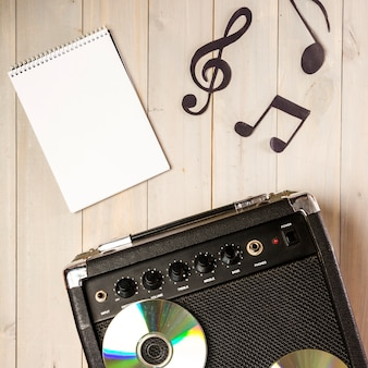 Spiral notizblock; musiknote und verstärker mit cd auf hölzernem schreibtisch
