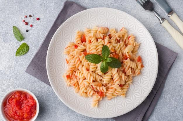 Spiral nudeln mit kirschtomaten und tomatensauce auf einem teller gemischt.