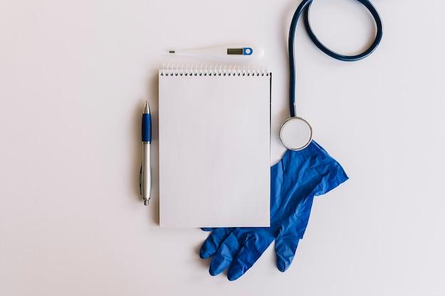 Spiralblock stift; stethoskop; thermometer und handschuhe auf weißer oberfläche