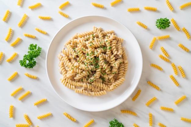 Spirali oder spiralnudeln pilzcremesauce mit petersilie - italienische küche