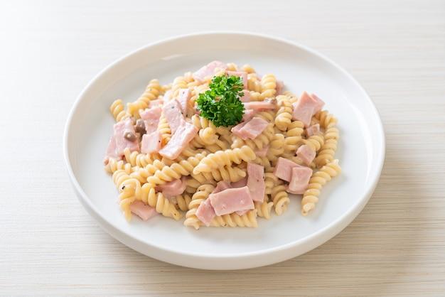 Spirali oder spiralnudeln pilzcremesauce mit schinken - italienische küche