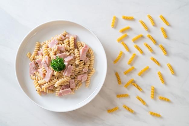 Spirali oder spiralnudeln pilzcremesauce mit schinken. italienischer essensstil
