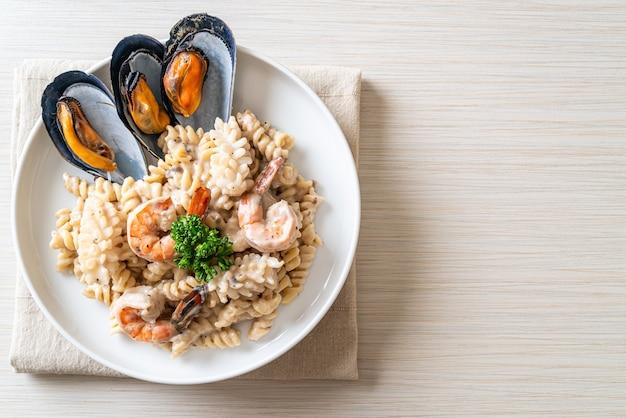 Spiralnudeln-pilz-sahnesauce mit meeresfrüchten - italienische küche -
