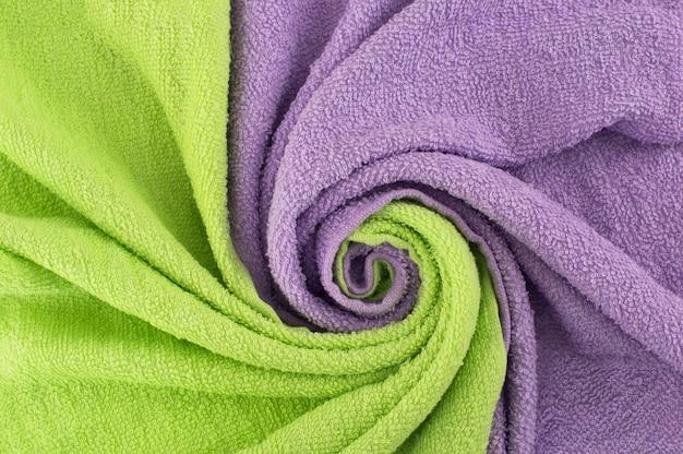 Spiraltextilien verdreht. hintergrund mit einer welle von hellgrünen und lila handtüchern.