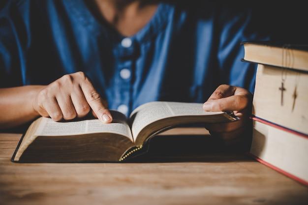 Spiritualität und religion, hände falteten sich im gebet auf einer heiligen bibel im kirchenkonzept für glauben.