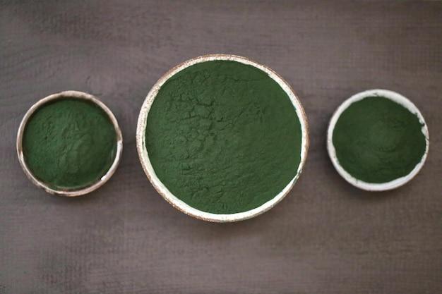 Spirulina-algen. trockenes pulver in runden tassen auf einem schwarzen tisch.