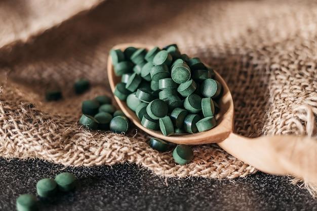 Spirulina-algentabletten auf einem holzlöffel auf einem sackleinenhintergrund. nahansicht
