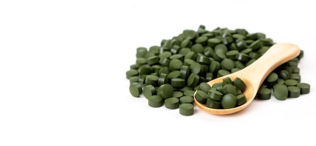 Spirulina-algentabletten mit löffel isoliert nahrungsergänzungsmittel vitamine gesundheitskonzept
