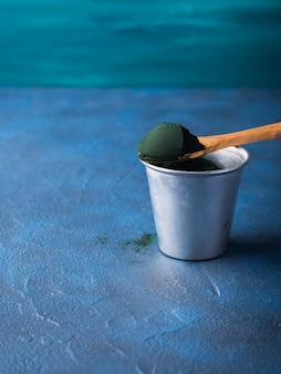 Spirulina pulver im löffel auf blauem hintergrund