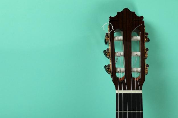 Spitze der klassischen gitarre auf minzhintergrund, nahaufnahme
