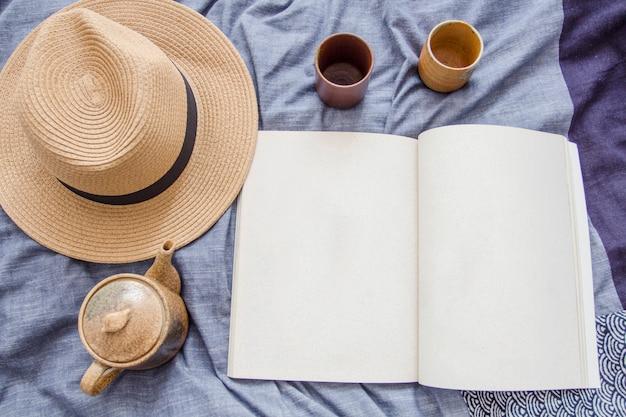 Spitze des öffnenden leeren buches oder der zeitschrift mit kaffee- u. teesatz und braunem hut in der flachen lage co