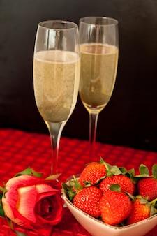 Spitzengläser champagner mit erdbeeren in einer schüssel und eine rose auf einer roten tischdecke