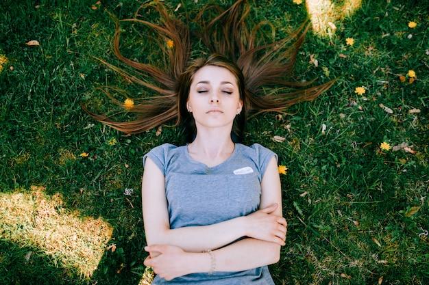 Spitzenporträt der schönen jungen langhaarigen brunettefrau, die auf grünem gras schläft