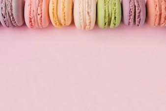Spitzenrand gemacht mit bunten Makronen auf rosa Hintergrund