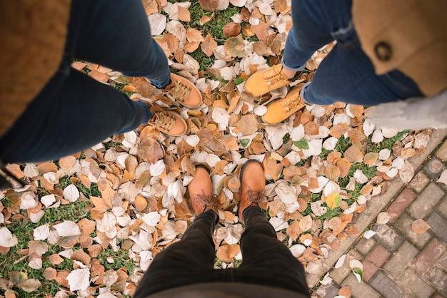 Spitzenschuß nah oben von den frauen in den stiefeln, die im park stehen