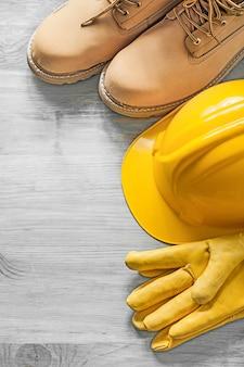 Spitzenstiefel schutzhelm lederschutzhandschuhe auf holzbrettkonstruktionskonzept