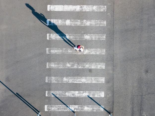 Spitzenvogelperspektive auf des mannes, der auf den zebrastreifen in der straße, zusammenfassung lokalisiertes design mit kopienraum geht