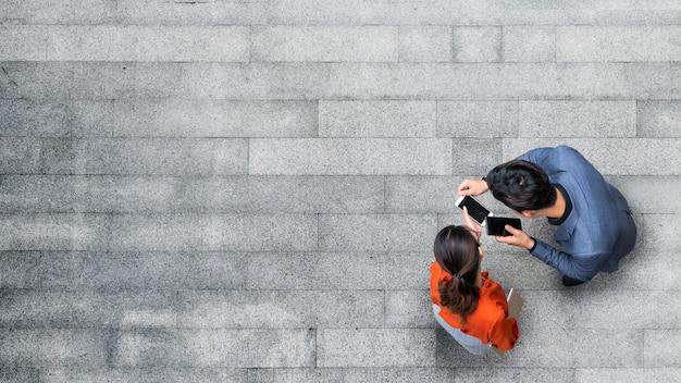 Spitzenvogelperspektive von den geschäftsmann- und frauenleuten, die smartphone treffen und verwenden.