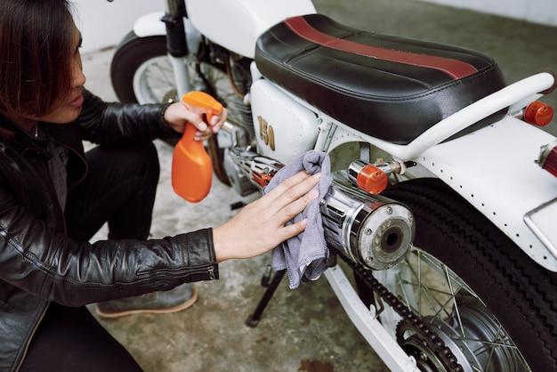 Spitzenwinkelsicht des geernteten radfahrers das rohr seines motorrades polierend