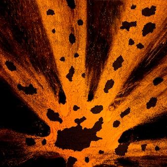 Splatter von orangem holi-pulver mit schwarzen flecken