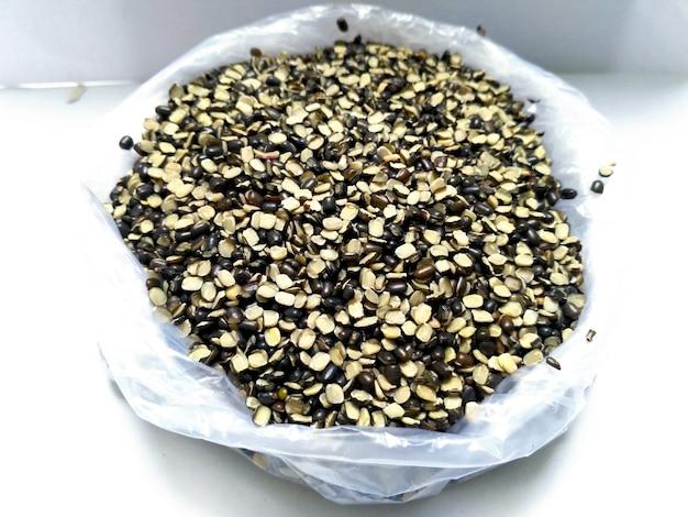 Split black lentil auch bekannt als black gram, black urad dal, vigna mungo, urad bean, urad dal, minapa pappu, mungo bean oder black matpe bean isoliert auf weißem hintergrund