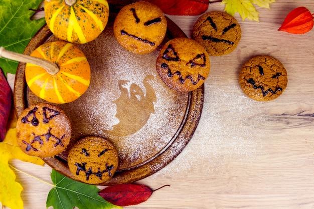 Spooky cupcakes, kürbis, blätter und silhouette der fledermaus auf holzschalen