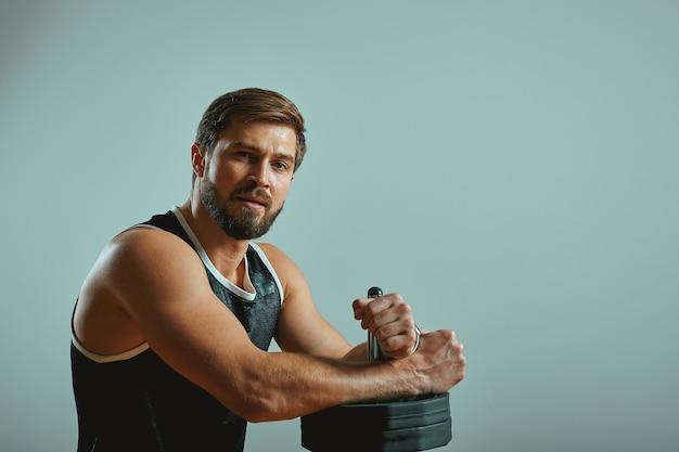 Sport, aktivität, gesundheit und fitness-konzept. geeigneter junger männlicher athlet, der mit barbell gegen grauen wandhintergrund mit kopienraum für ihren inhalt steht