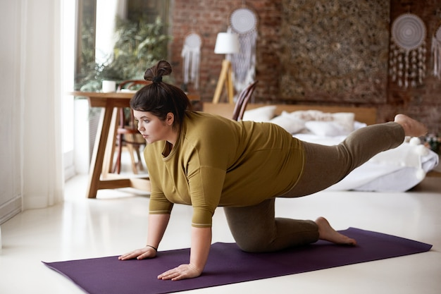 Sport-, aktivitäts-, fitness- und gewichtsverlustkonzept. innenbild einer konzentrierten selbstbestimmten jungen frau in übergröße in leggings und t-shirt, die auf der matte trainiert, ein bein anhebt und versucht, das gleichgewicht zu halten