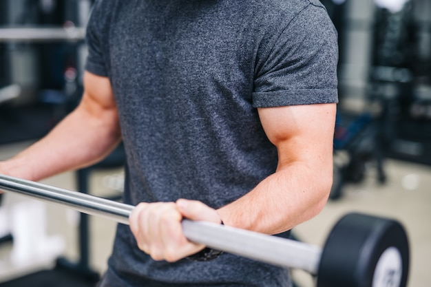 Sport-, bodybuilding-, lebensstil- und leutekonzept - junger mann, der barbell anhebt und muskelnahaufnahme biegt. hände des starken mannes an der turnhalle.
