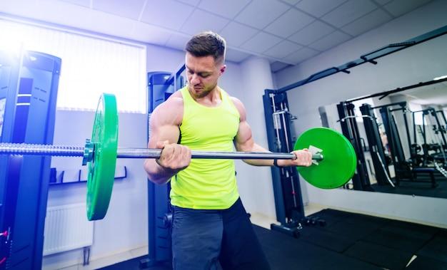Sport-, bodybuilding-, lebensstil- und leutekonzept - junger mann mit dem barbell, der muskeln biegt und schulterpresse in der turnhalle hockt.