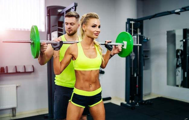 Sport-, bodybuilding-, lebensstil- und leutekonzept - junger mann und frau mit dem barbell, der muskeln biegt und schulterpresse in der turnhalle hockt.