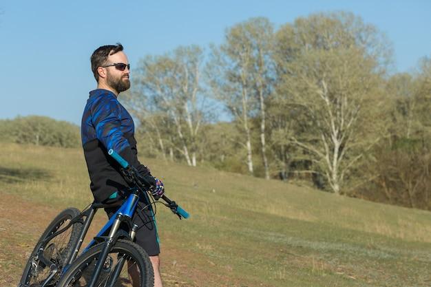Sport brutaler bärtiger kerl auf einem modernen mountainbike schöne aussicht vom berg