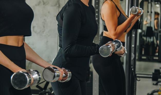 Sport, eignung, bodybuilding, gewichtheben und leutekonzept - nah oben von der frau, die arme mit dummkopf in der turnhalle biegt.