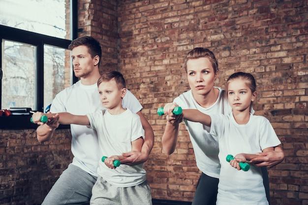Sport-familie, die übungen mit dummköpfen tut.