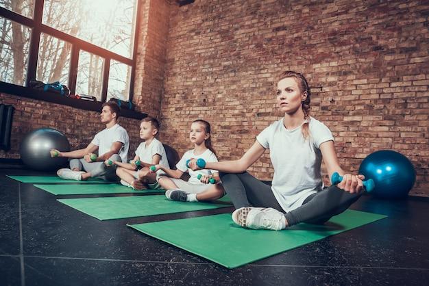 Sport-familie sitzen auf turnhallenteppichen im fitness-club.