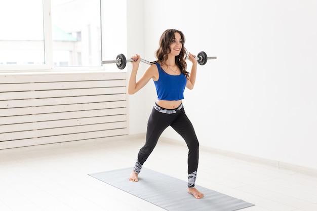 Sport-, fitness- und menschenkonzept - schöne junge frau, die mit langhantel hocken trainiert.