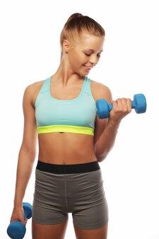 Sport-, fitness- und personenkonzept: frau in der sportausrüstungspraxis mit handgewichten lokalisiert auf weißem hintergrund