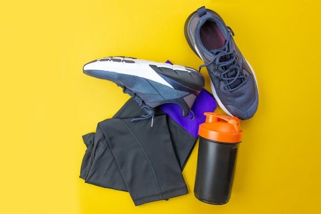 Sport flaches layout. fitnesszubehör turnschuhe, kleidung, flasche auf gelbem hintergrund. sport und fitness zu hause machen.