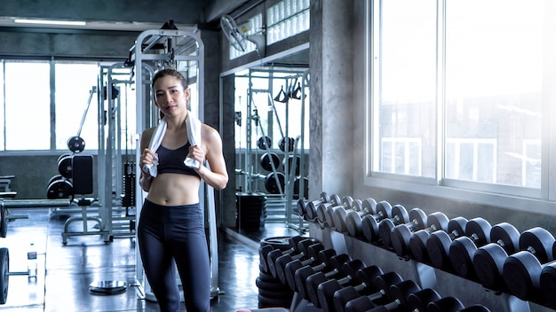 Sport-frau, die dummköpfe und trainings-übungen in der turnhalle anhebt - lebensstil und gesundheitspflege con
