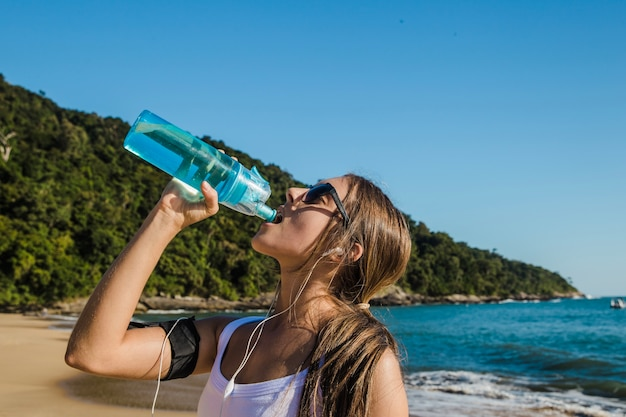 Sport frau trinkt wasser am strand