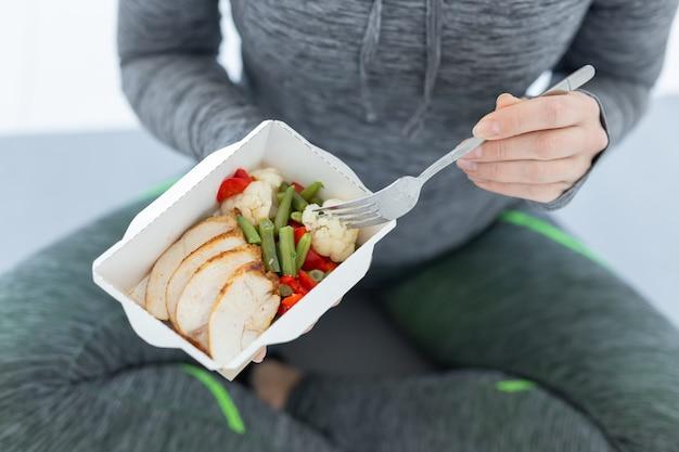 Sport, gesund, menschen konzept - nahaufnahme des mädchens, das diätkost nach fitnesstraining hält, draufsicht