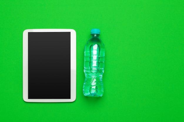 Sport, gesunde lebensweise und objekte konzept - nahaufnahme von tablet pc-computer mit wasserflasche
