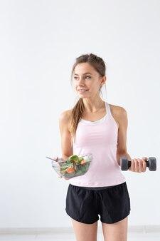 Sport, gesunder lebensstil, menschenkonzept - junge brünette frau mit salat und einer hantel. sie lächelt und genießt den gesunden lebensstil.