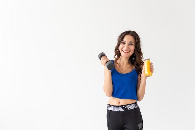 Sport, gesunder lebensstil, menschenkonzept - junge frau mit einer hantel in der hand und einer flasche saft in der anderen hand auf weißem hintergrund mit kopierraum