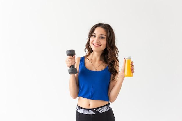Sport, gesunder lebensstil, menschenkonzept - junge frau mit einer hantel in der hand und einer flasche saft in der anderen hand.