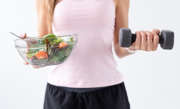 Sport, gesunder lebensstil, menschenkonzept - nahaufnahme einer jungen frau mit salat und einer hantel. sie lächelt und genießt den gesunden lebensstil