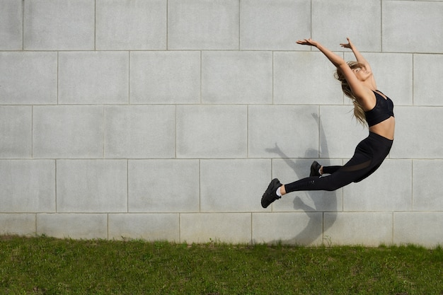 Sport, gesundheit, aktivität, fitness, wohlbefinden und sommerkonzept. freeze action shot der schönen jungen kaukasischen sportlerin in stilvollen schwarzen kleidern, die beim aufwärmen im freien hoch springen