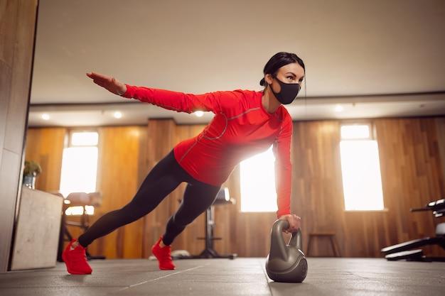 Sport girl in mask von coronavirus macht kettlebells planking.